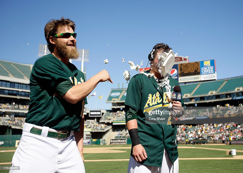 Josh Reddick #16 of the Oakland Athletics throws a cream pie in the face of Josh Donaldson #20 of the Oakland Athletics after Donaldson hit the game-winning hit in the 11th inning of their game against the Boston Red Sox at O.co Coliseum on July 14, 2013 in Oakland, California.