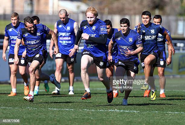 Josh Reynolds James Graham and Michael Ennis race during a Canterbury Bulldogs NRL training session at Belmore Sports Ground on July 29 2014 in...