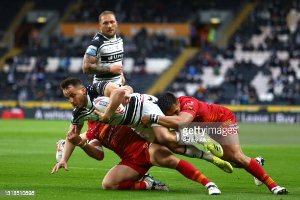 Josh Reynolds of Hull FC is tackled by two Catalans Dragons players during the Betfred Super League round 6 match between Hull FC and Catalans...