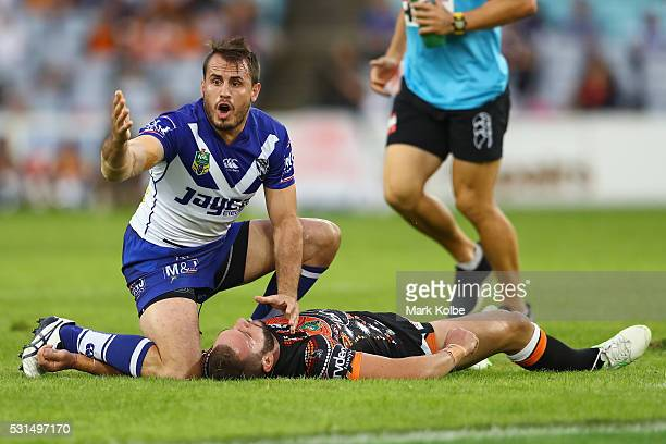 Josh Reynolds of the Bulldogs calls for assistance for an injured Robbie Farah of the Tigers during the round 10 NRL match between the Wests Tigers...