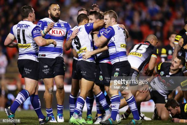 Josh Reynolds of the Bulldogs celebrates with team mates after scoring a try during the round 21 NRL match between the Penrith Panthers and the...