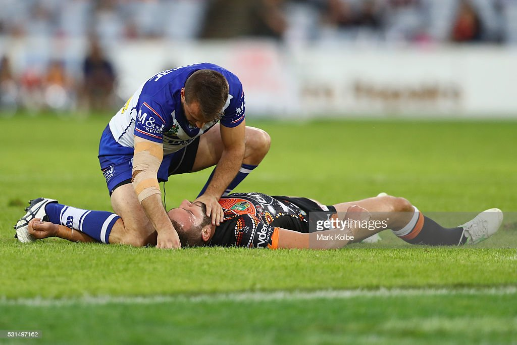 Josh Reynolds of the Bulldogs shows concern for an injured Robbie Farah of the Tigers during the round 10 NRL match between the Wests Tigers and the Canterbury Bulldogs at ANZ Stadium on May 15, 2016 in Sydney, Australia.