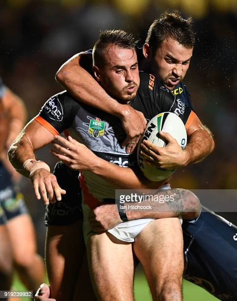 Josh Reynolds of the Tigers is tackled by Sam Hoare and Ethan Lowe of the Cowboys during the NRL trial match between the North Queensland Cowboys and...