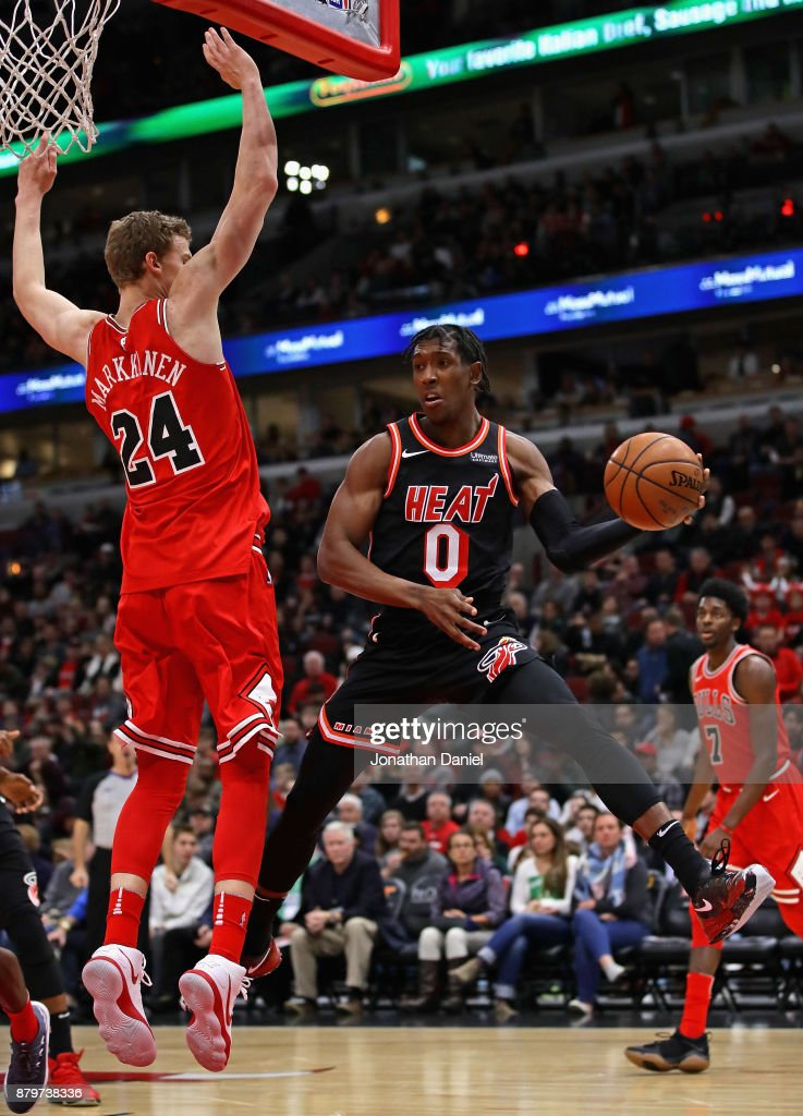 Josh Richardson #0 of the Miami Heat leaps to pass around Lauri Markkanen #24 of the Chicago Bulls at the United Center on November 26, 2017 in Chicago, Illinois.
