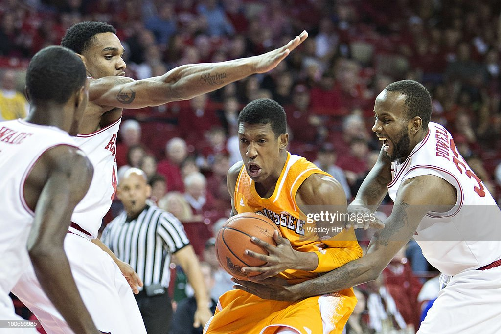 Josh Richardson #1 of the Tennessee Volunteers drives to the basket and is fouled by Marshawn Powell #33 of the Arkansas Razorbacks at Bud Walton Arena on February 2, 2013 in Fayetteville, Arkansas. The Razorbacks defeated the Volunteers 73-60.