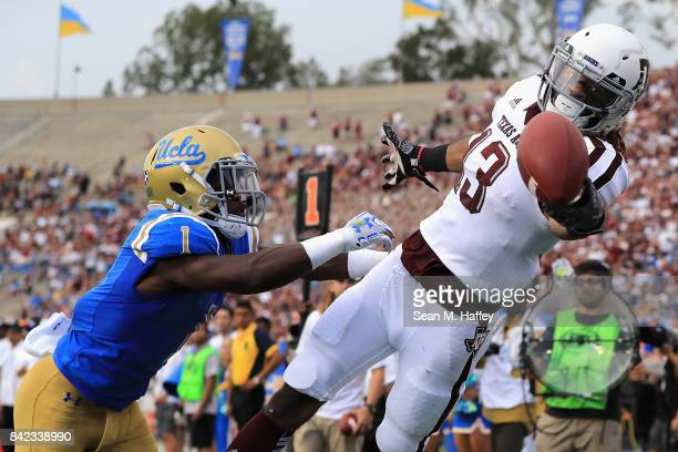 Josh Rogers of the Texas AM Aggies is unable to catch this pass as Darnay Holmes of the UCLA Bruins defends during the first half of a game at the...