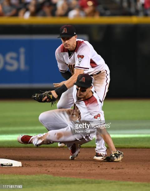 Josh Rojas and Nick Ahmed of the Arizona Diamondbacks collide behind second base while fielding a ground ball hit by Ty France of the San Diego...