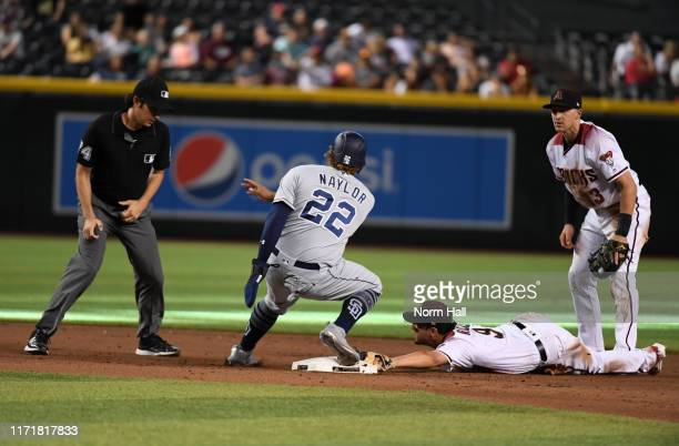 Josh Rojas of the Arizona Diamondbacks and Josh Naylor of the San Diego Padres look at second base umpire John Tumpane and wait for a call on a play...