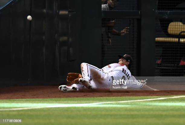 Josh Rojas of the Arizona Diamondbacks attempts to make a sliding catch on a foul ball hit by Josh Naylor of the San Diego Padres during the sixth...