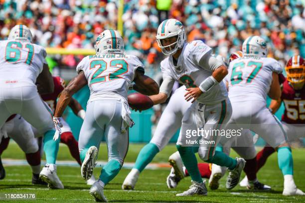 Josh Rosen of the Miami Dolphins hands the ball to Mark Walton against the Washington Redskins in the scond quarter at Hard Rock Stadium on October...