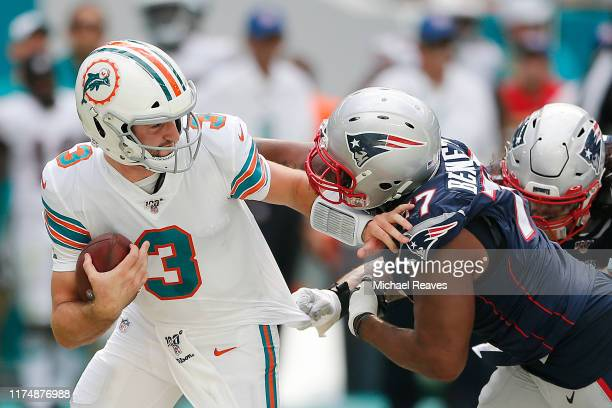 Josh Rosen of the Miami Dolphins is sacked by Michael Bennett of the New England Patriots during the fourth quarter at Hard Rock Stadium on September...