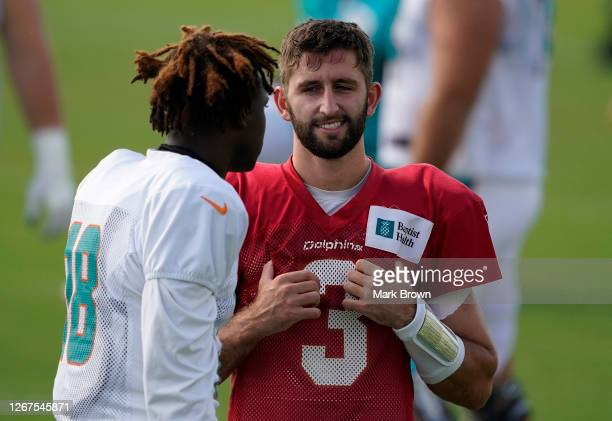 Josh Rosen of the Miami Dolphins speaks with Preston Williams before training camp at Baptist Health Training Facility at Nova Southern University on...
