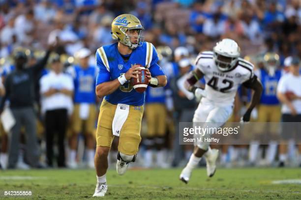 Josh Rosen of the UCLA Bruins is flushed from the pocket as Otaro Alaka of the Texas AM Aggies pursues him during the second half of a game at the...