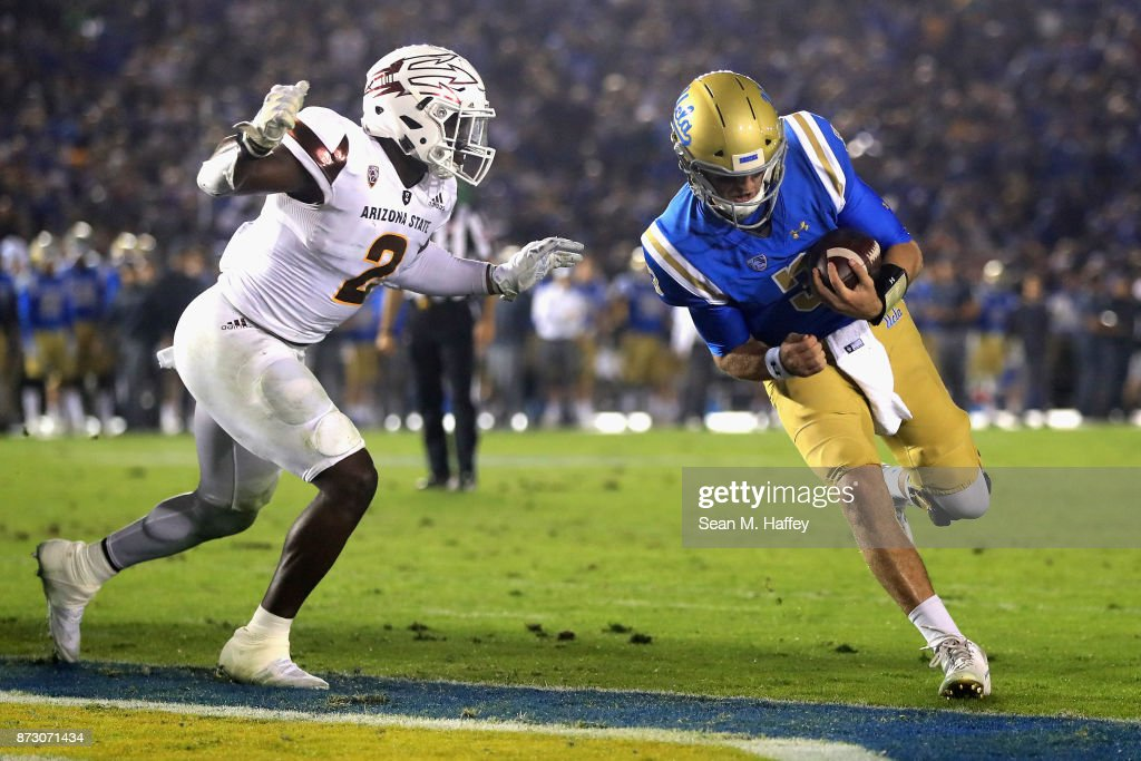 Josh Rosen #3 of the UCLA Bruins runs past Christian Sam #2 of the Arizona State Sun Devils for a touchdown during the first half of a game at the Rose Bowl on November 11, 2017 in Pasadena, California.