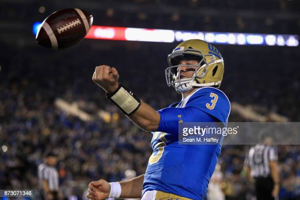 Josh Rosen of the UCLA Bruins tosses the ball after scoring a touchdown on a short run during the first half of a game against the Arizona State Sun...