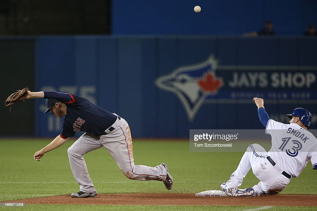 Josh Rutledge #30 of the Boston Red Sox cannot handle a throw to second base in the sixth inning during MLB game action as Justin Smoak #13 of the Toronto Blue Jays slides safely into second base on September 18, 2015 at Rogers Centre in Toronto, Ontario, Canada.