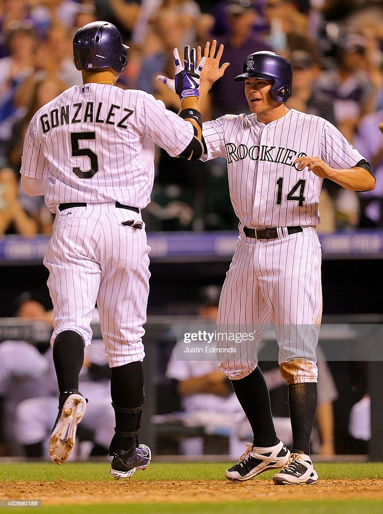 Josh Rutledge #14 of the Colorado Rockies greets Carlos Gonzalez #5 after he hit a two-run home runs during the seventh inning against the Pittsburgh Pirates at Coors Field on July 25, 2014 in Denver, Colorado.