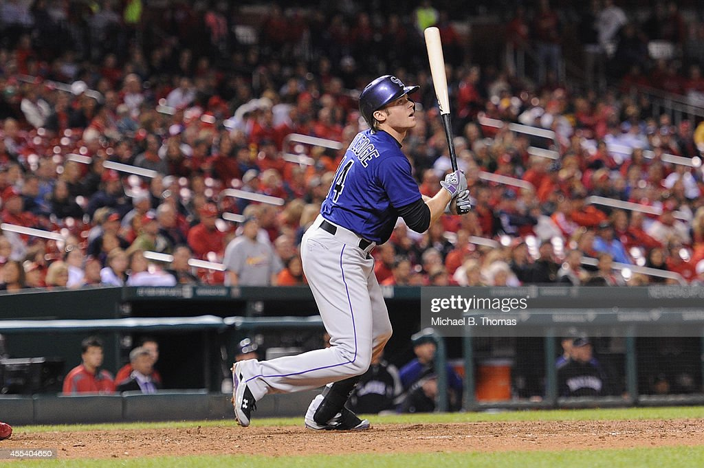 Josh Rutledge #14 of the Colorado Rockies hits a sacrifice fly against the St. Louis Cardinals in the ninth inning at Busch Stadium on September 13, 2014 in St. Louis, Missouri. The Cardinals defeated the Rockies 5-4.