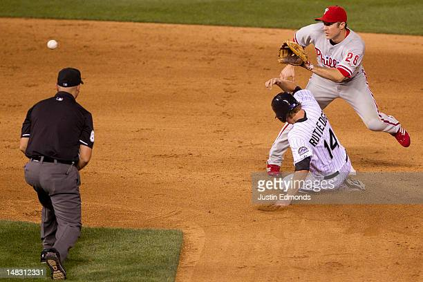 Josh Rutledge of the Colorado Rockies steals second base ahead of the tag by Chase Utley of the Philadelphia Phillies under the watchful eye of...
