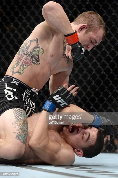 Josh Sampo punches Ryan Benoit in their flyweight fight during The Ultimate Fighter season 18 live finale inside the Mandalay Bay Events Center on...