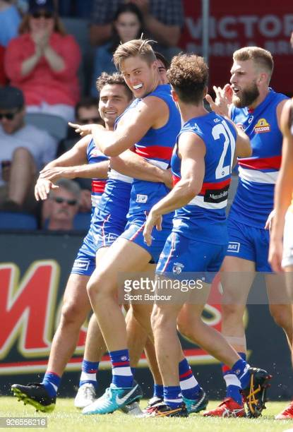 Josh Schache of the Bulldogs is congratulated by his teammates after kicking his first goal during the AFL JLT Community Series match between the...