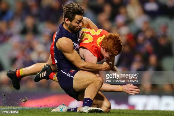 Josh Schoenfeld of the Suns is tackled by Lachie Weller of the Dockers during the round 20 AFL match between the Fremantle Dockers and the Gold Coast...