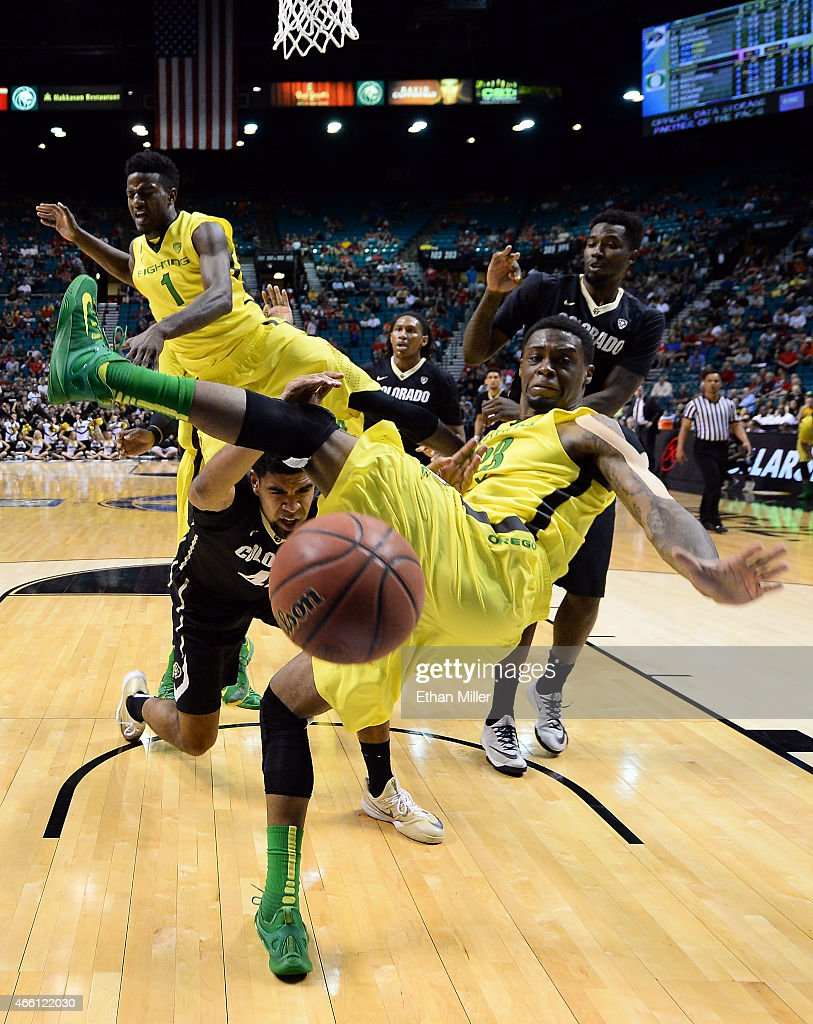 Josh Scott #40 of the Colorado Buffaloes drives to the basket against Elgin Cook #23 and Jordan Bell #1 of the Oregon Ducks during a quarterfinal game of the Pac-12 Basketball Tournament at the MGM Grand Garden Arena on March 12, 2015 in Las Vegas, Nevada. Oregon won 93-85.
