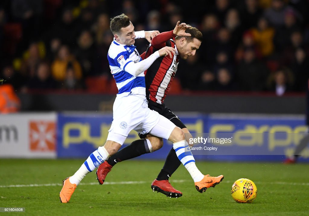 Josh Scowen of Queens Park Rangers is challenged by Billy Sharp of Sheffield United during the Sky Bet Championship match between Sheffield United and Queens Park Rangers at Bramall Lane on February 20, 2018 in Sheffield, England.