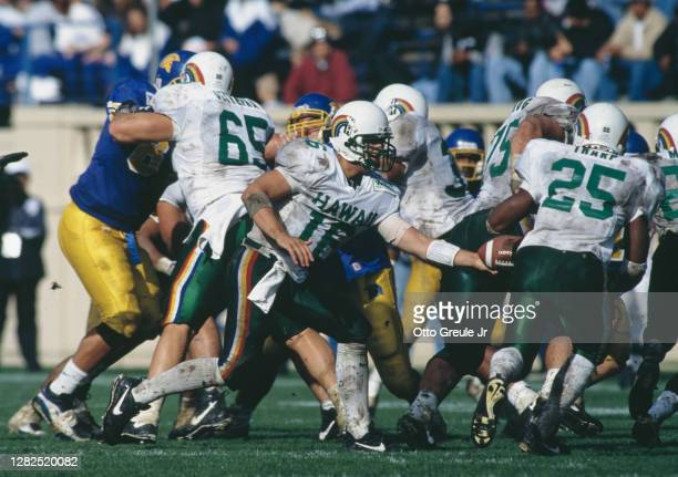 Josh Skinner, Quarterback for the Hawaii Rainbow Warriors hands the football off to Running Back Charles Tharp during the NCAA Western Athletic...