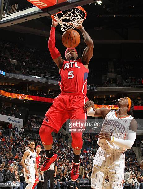 Josh Smith of the Atlanta Hawks dunks over Gerald Wallace of the Charlotte Bobcats on January 22 2011 at Time Warner Cable Arena in Charlotte North...