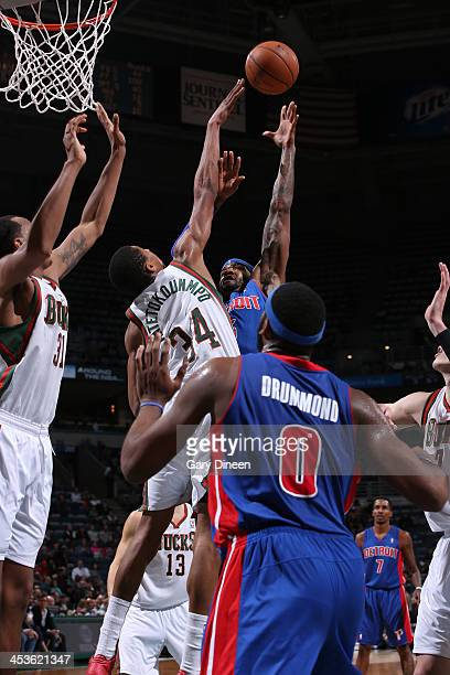 Josh Smith of the Detroit Pistons shoots against Giannis Antetokounmpo of the Milwaukee Bucks on December 4 2013 at the BMO Harris Bradley Center in...