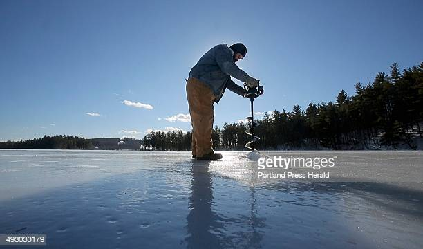 Josh Sparks uses an electric auger to drill a hole in ice on Lower Range Pond in Poland on Thursday January 9 2014