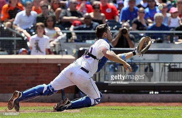 Josh Thole of the New York Mets dives to catch a seventh inning bunt attempt by Wilson Valdez of the Cincinnati Reds at Citi Field on June 17 2012 in...
