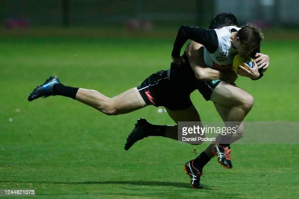 Josh Thomas is tackled by Brayden Maynard during a Collingwood Magpies AFL training session at Holden Centre on June 04, 2020 in Melbourne, Australia.