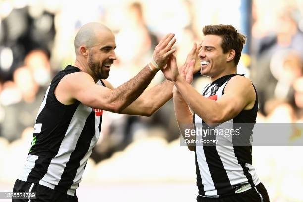 Josh Thomas of the Magpies is congratulated by Steele Sidebottom of the Magpies after scoring a goal during the round 15 AFL match between the...