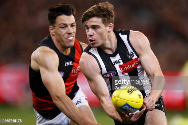 Josh Thomas of the Magpies runs with the ball during the round 23 AFL match between the Collingwood Magpies and the Essendon Bombers at Melbourne...