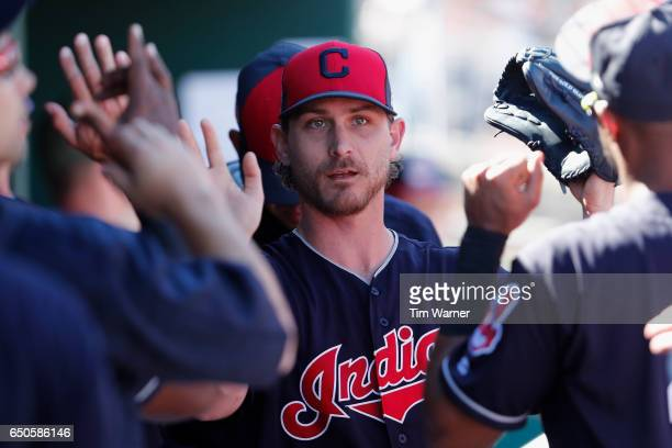 Josh Tomlin of the Cleveland Indians is greeted by teammates after exiting the game in the fourth inning during the spring training game against the...
