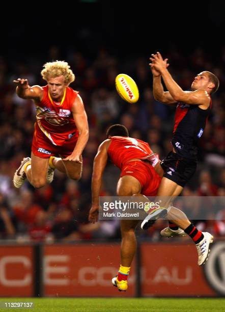 Josh Toy and Karmichael Hunt of the Suns contest a mark with David Zaharakis of the Bombers during the round six AFL match between the Essendon...