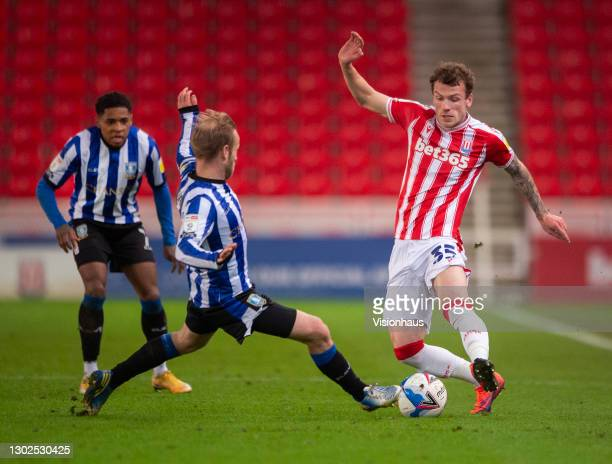 Josh Tymon of Stoke City and Barry Bannan of Sheffield Wednesday in action during the Sky Bet Championship match between Stoke City and Sheffield...