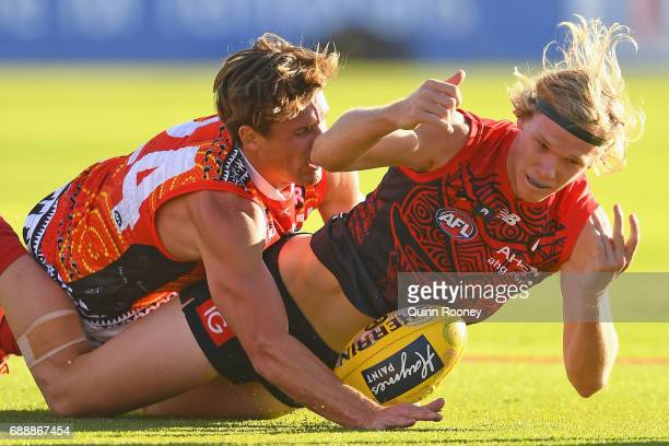 Josh Wagner of the Demons handballs whilst being tackled by David Swallow of the Suns during the round ten AFL match between the Melbourne Demons and...