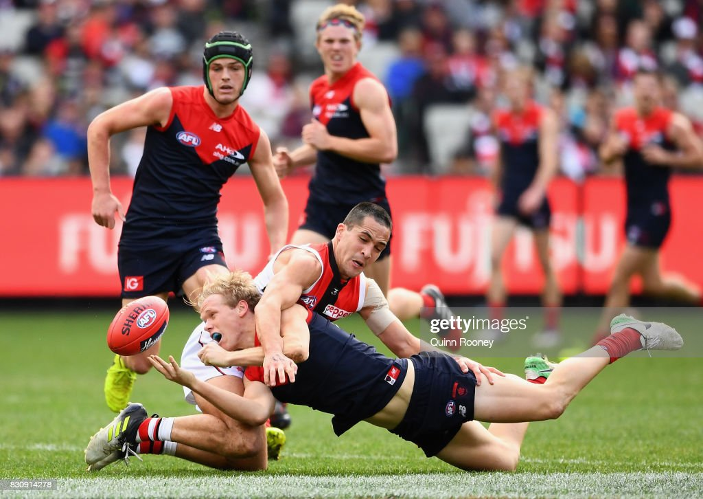 Josh Wagner of the Demons handballs whilst being tackled by Shane Savage of the Saints during the round 21 AFL match between the Melbourne Demons and the St Kilda Saints at Melbourne Cricket Ground on August 13, 2017 in Melbourne, Australia.