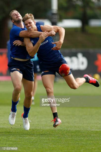 Josh Walker and Mason Wood compete during a North Melbourne Kangaroos AFL training session at Arden Street Ground on March 19, 2020 in Melbourne,...