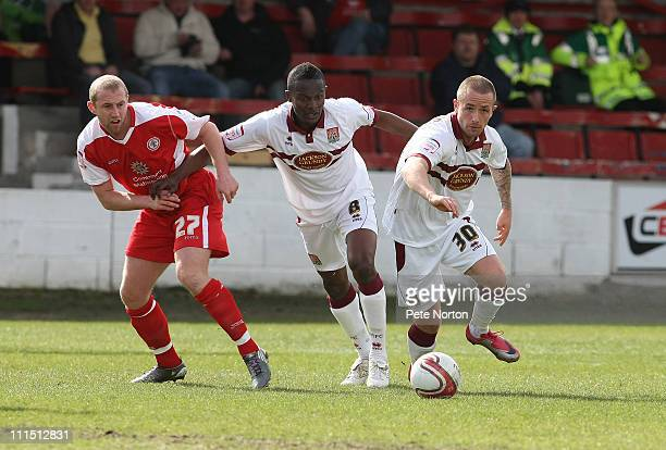 Josh Walker of Northampton Town moves away with the ball as team mate Abdul Osman and Ian Craney of Accrington Stanley look on during the npower...