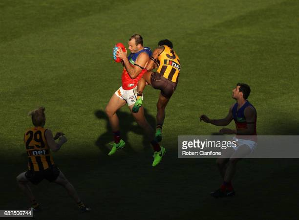 Josh Walker of the Lions is challenged by Cyril Rioli of the Hawks during the round eight AFL match between the Hawthorn Hawks and the Brisbane Lions...