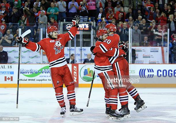 Josh Wesley of the Niagara IceDogs celebrates a goal with Graham Knott and Blake Siebenaler during the second period in Game Four of the 2016 OHL...