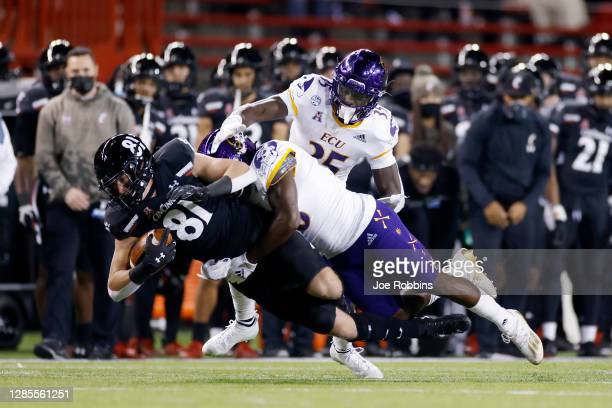 Josh Whyle of the Cincinnati Bearcats dives for yardage after a reception against Bruce Bivens of the East Carolina Pirates in the first quarter of...