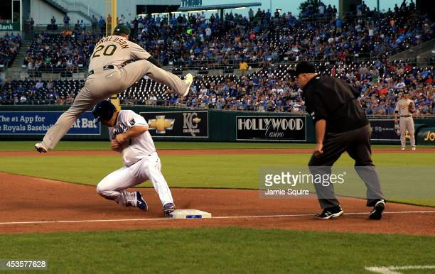 Josh Willingham of the Kansas City Royals slides into third after a wild throw as Josh Donaldson of the Oakland Athletics tries to tag him out during...