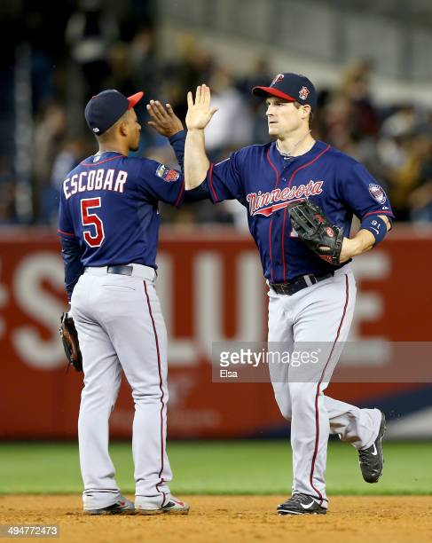 Josh Willingham of the Minnesota Twins celebrates the win with teammate Eduardo Escobar after the game against the New York Yankees on May 30 2014 at...