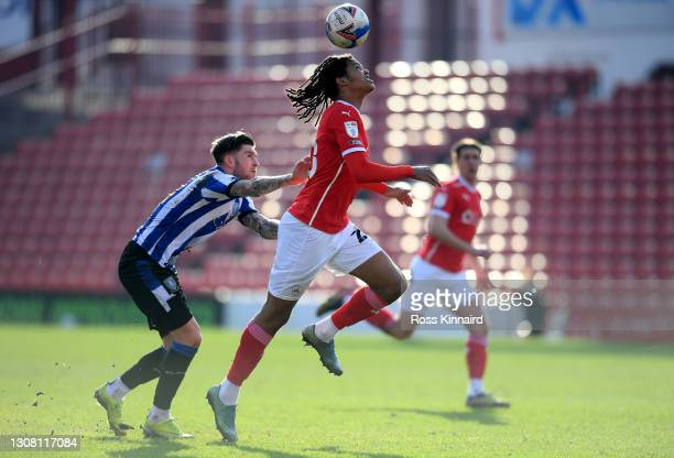 Josh Windass of Sheffield Wednesday and Toby Sibbick of Barnsley FC battle for the ball during the Sky Bet Championship match between Barnsley and...