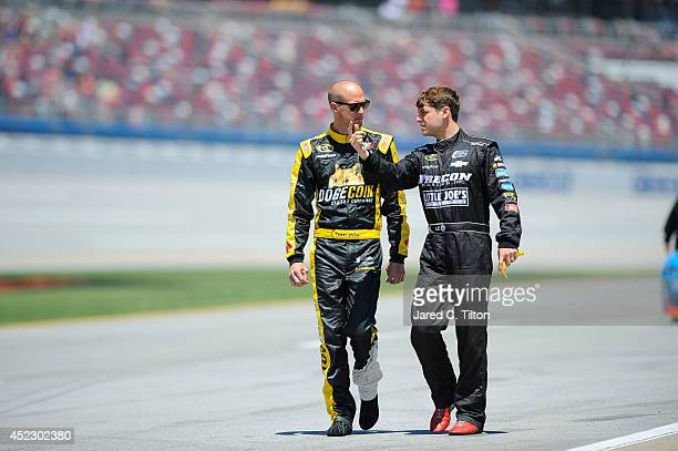 Josh Wise driver of the DogecoinRedditcom Chevrolet talks to Landon Cassill driver of the Hillman Racing Chevrolet during qualifying for the NASCAR...